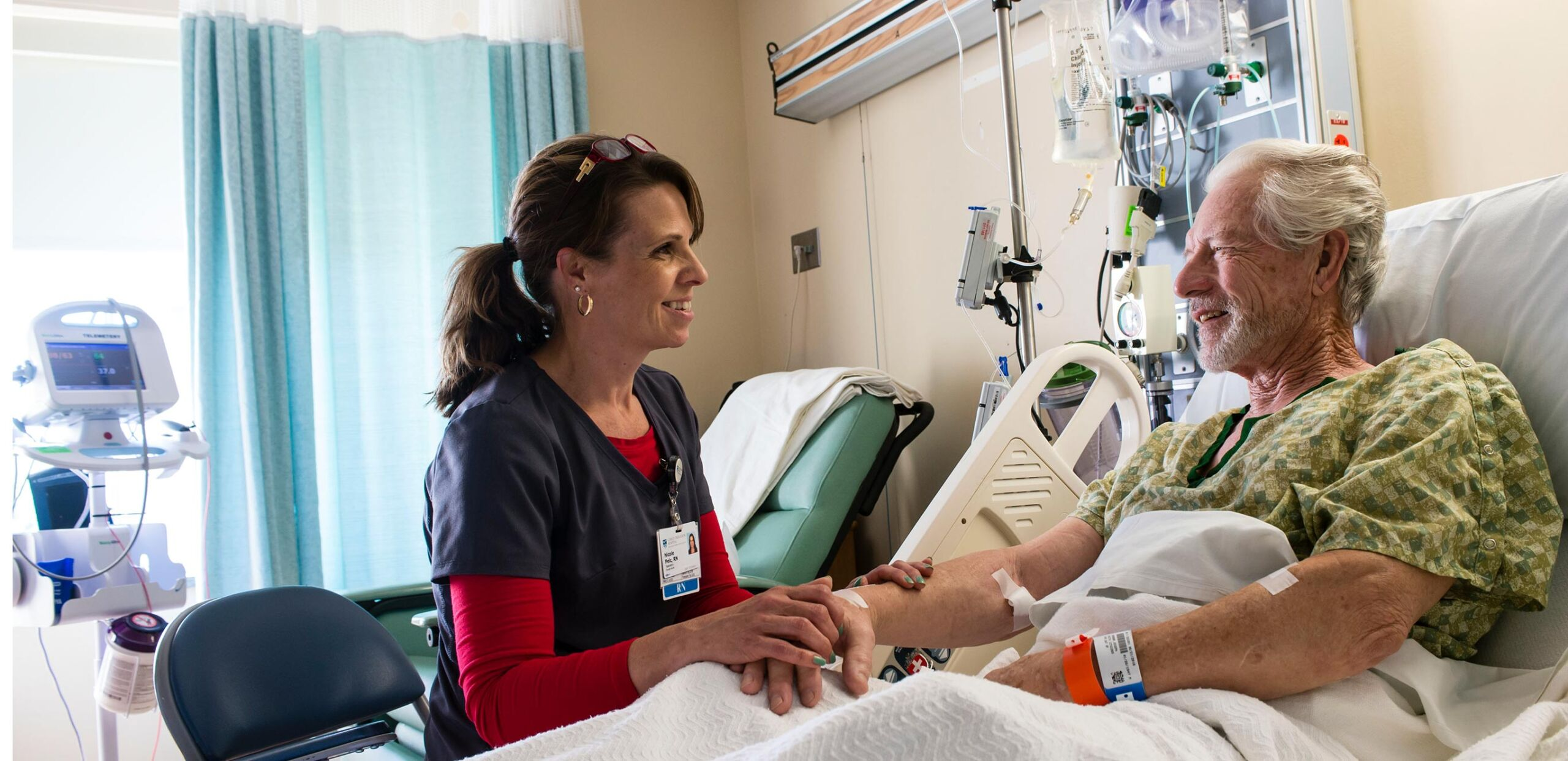 Friendly female nurse holds hand of smiling older male patient while they talk in his room at Cooley Dickinson Hospital, 30 Locust Street, Northampton, MA 01060.