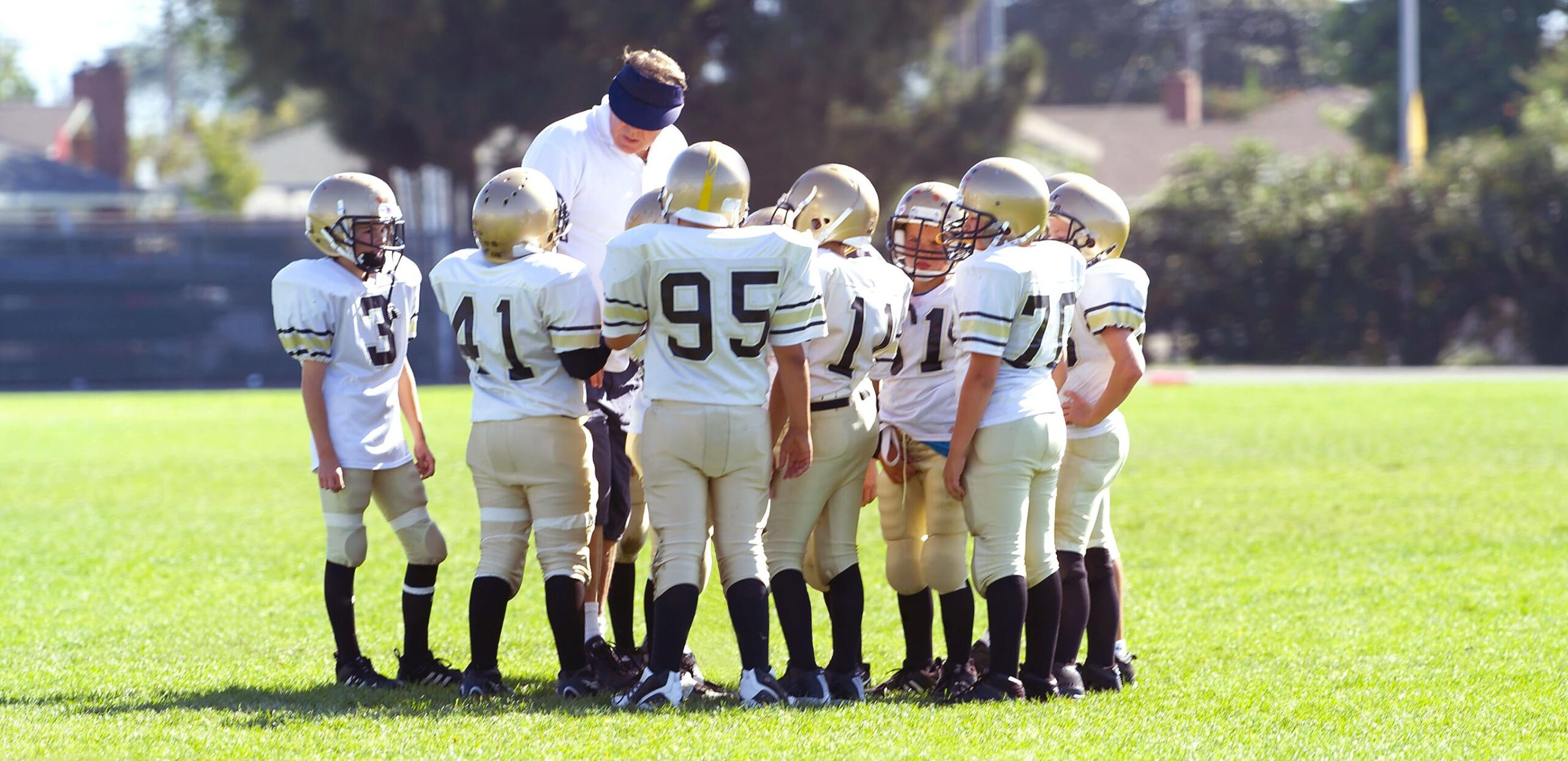 Elementary school football players huddle with their coach.