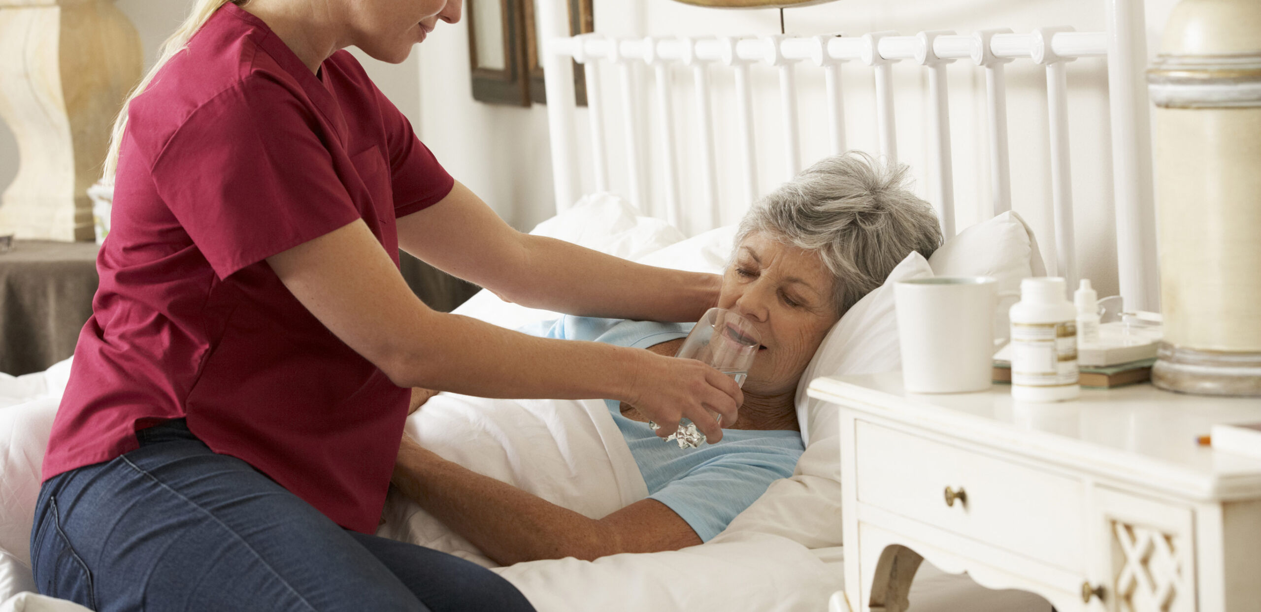 A palliative care provider helps a bed-bound patient take a sip of water from a glass in her home, Cooley Dickinson Medical Group VNA & Hospice, Northampton, MA 01060.