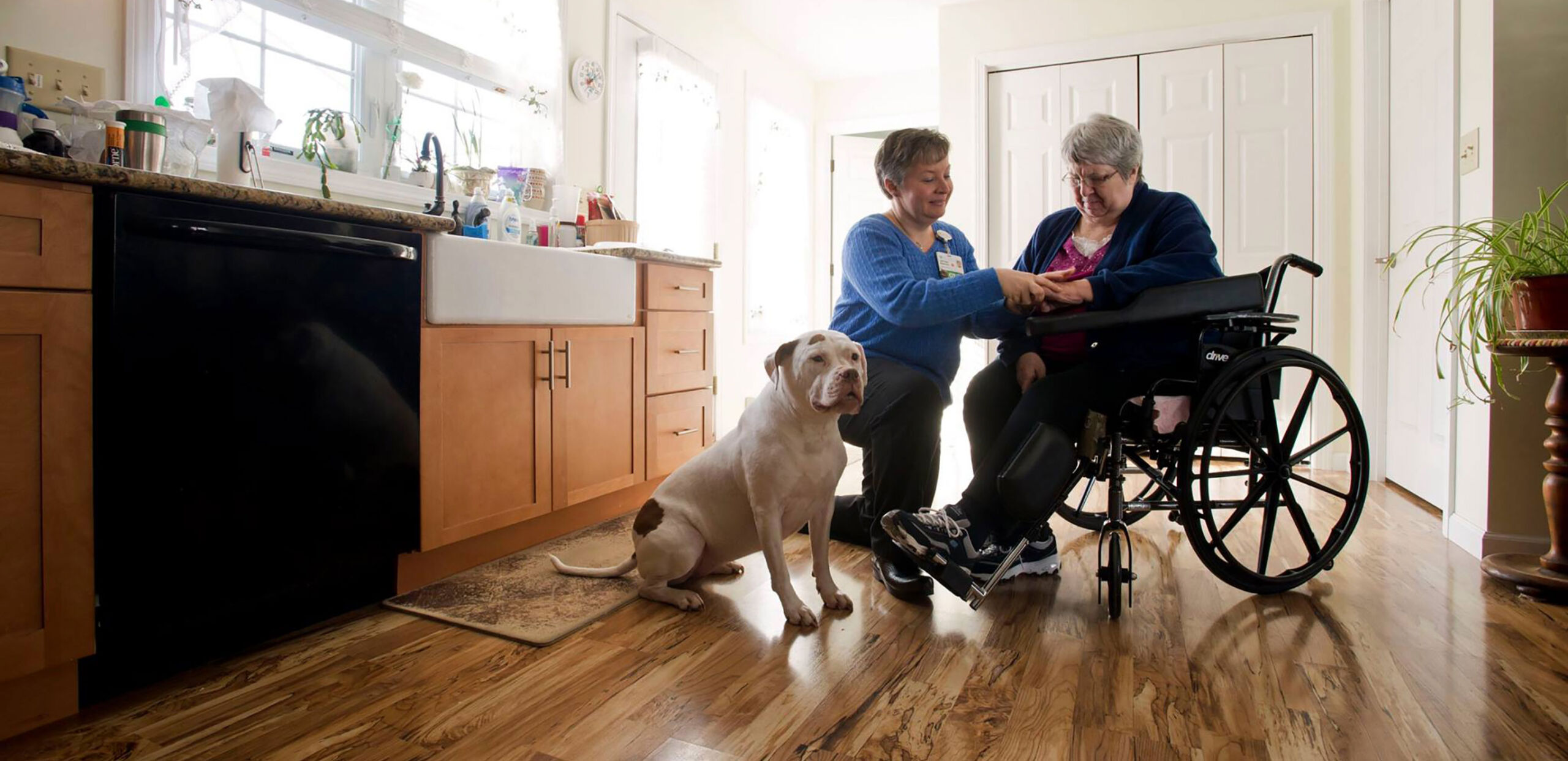 Visiting nurse talks with female patient in wheelchair in her home, Cooley Dickinson VNA & Hospice, Northampton, MA 01060.