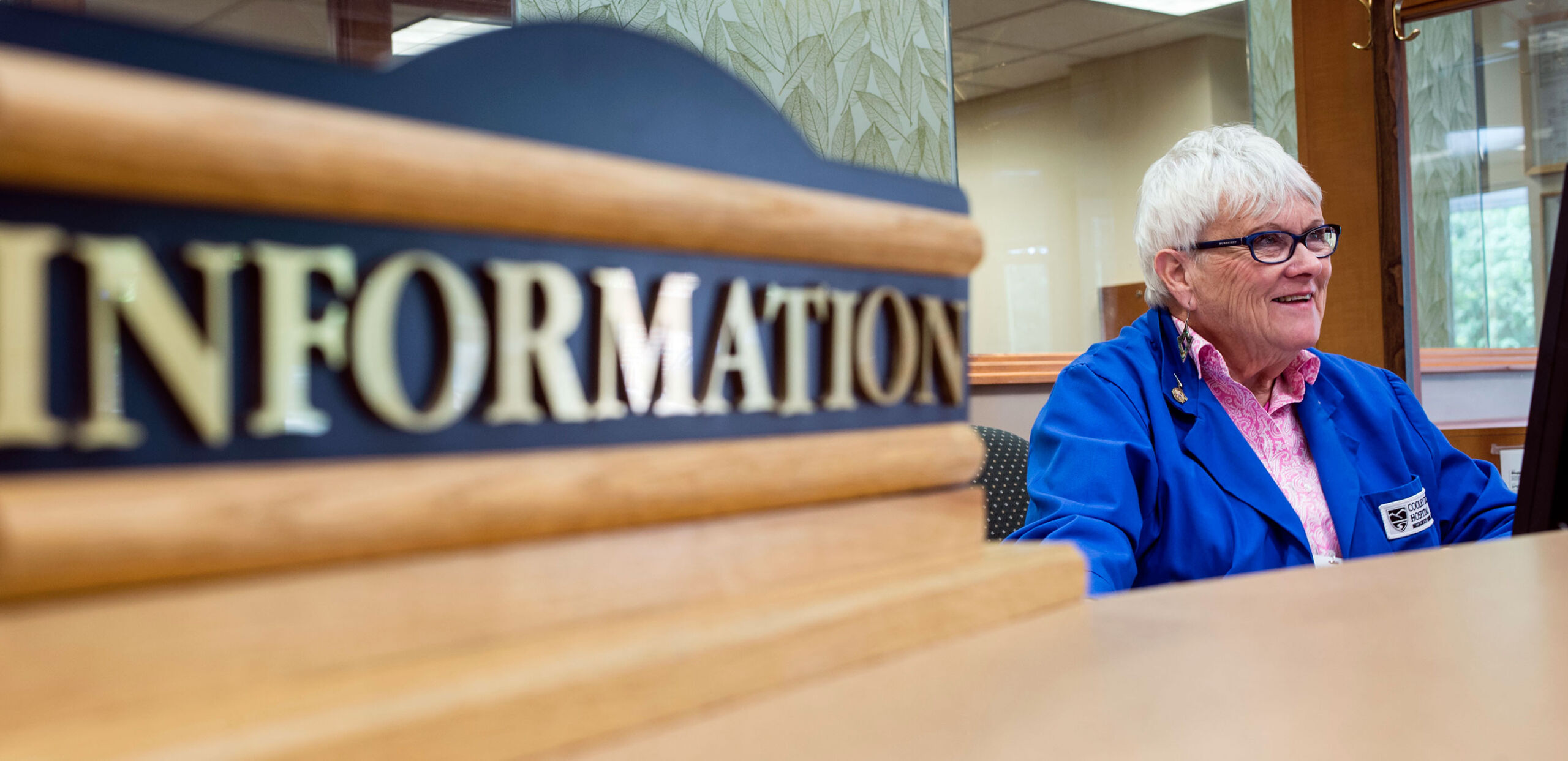 A volunteer greets visitors to the information desk at Cooley Dickinson Hospital, 30 Locust Street, Northampton, MA 01060.