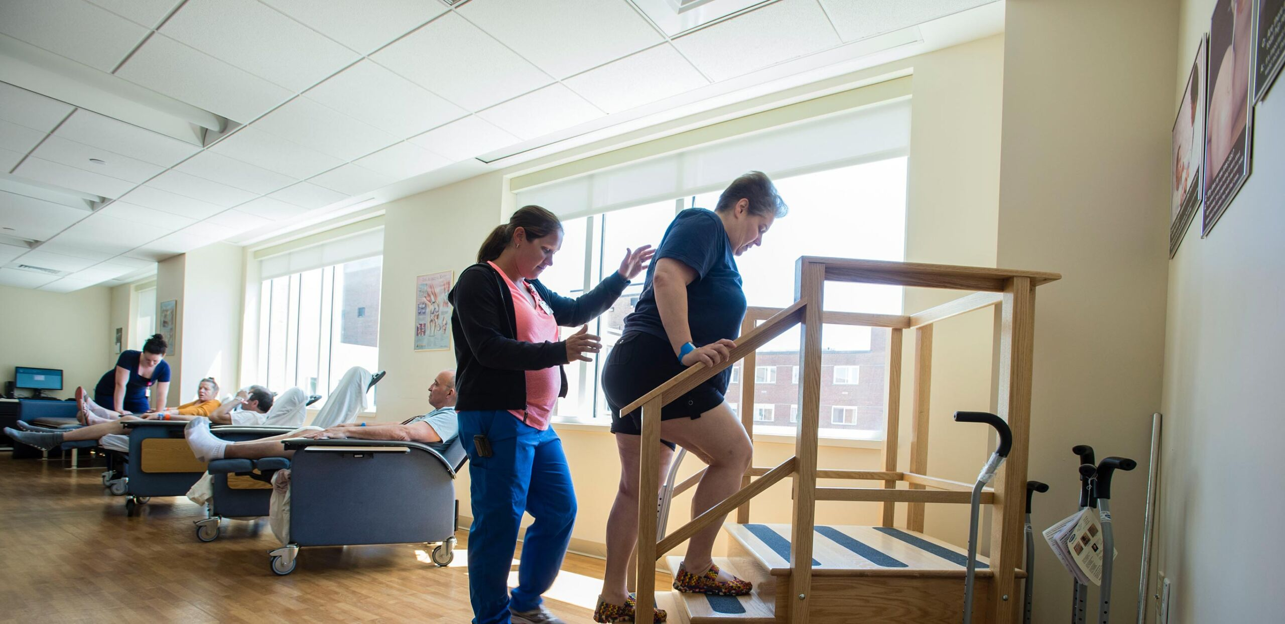 Physical therapist assists a patient as she practices climbing stairs after knee replacement at Cooley Dickinson Medical Group Orthopedics & Sports Medicine, West Hatfield, MA 01088.