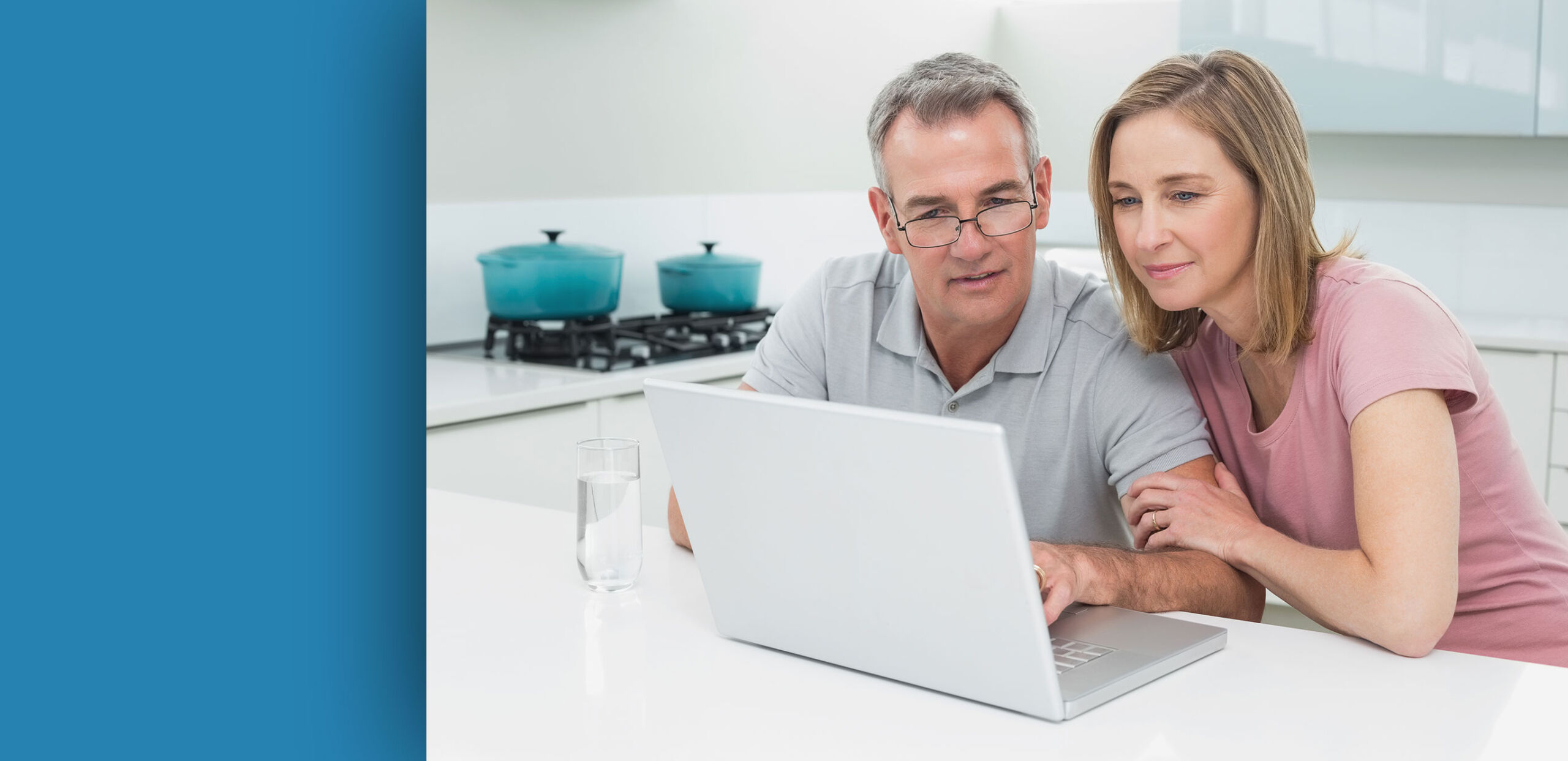 Man and woman looking at laptop computer in their kitchen, Cooley Dickinson Medical Group Plastic Surgery, Florence, MA 01062.