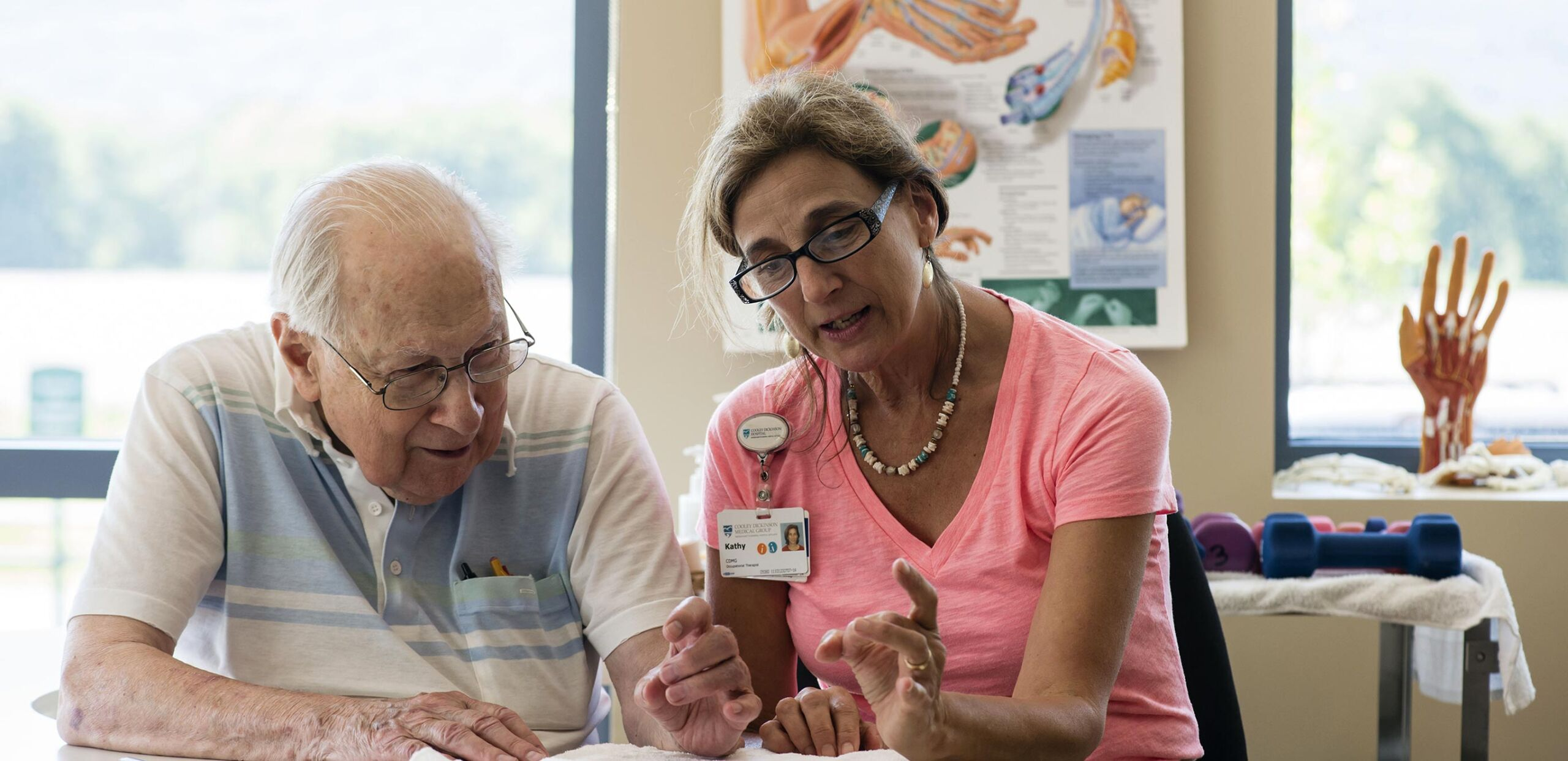 A certified hand therapist helps an elderly patient practice finger-dexterity exercises at Cooley Dickinson Rehabilitation Services, Northampton, MA 01060.