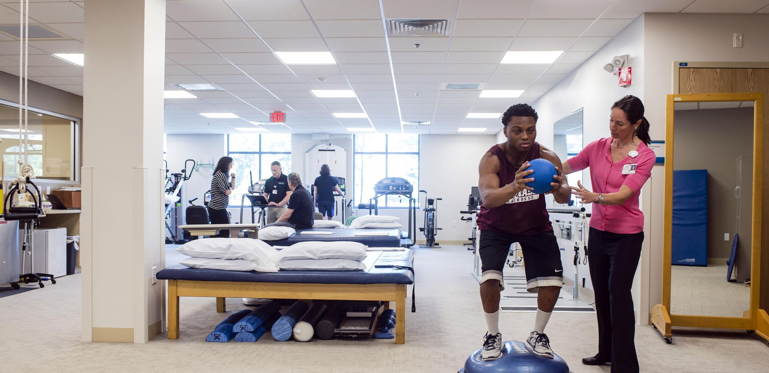 Female physical therapist helps male patient perform balance exercises, Rehabilitation Services at Cooley Dickinson Health Care include Physical Therapy, Occupational Therapy and Speech and Language Pathology.