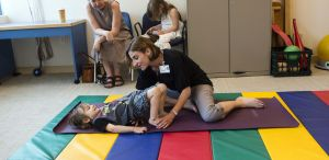 Occupational therapist works with young patient on floor exercises at Cooley Dickinson Rehabilitation Services, Northampton, MA 01060.