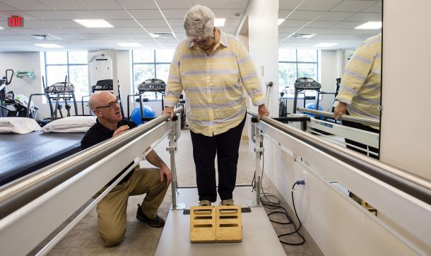 Physical therapist in Rehabilitation Services at Cooley Dickinson Health Care helps female patient practice walking and climbing.