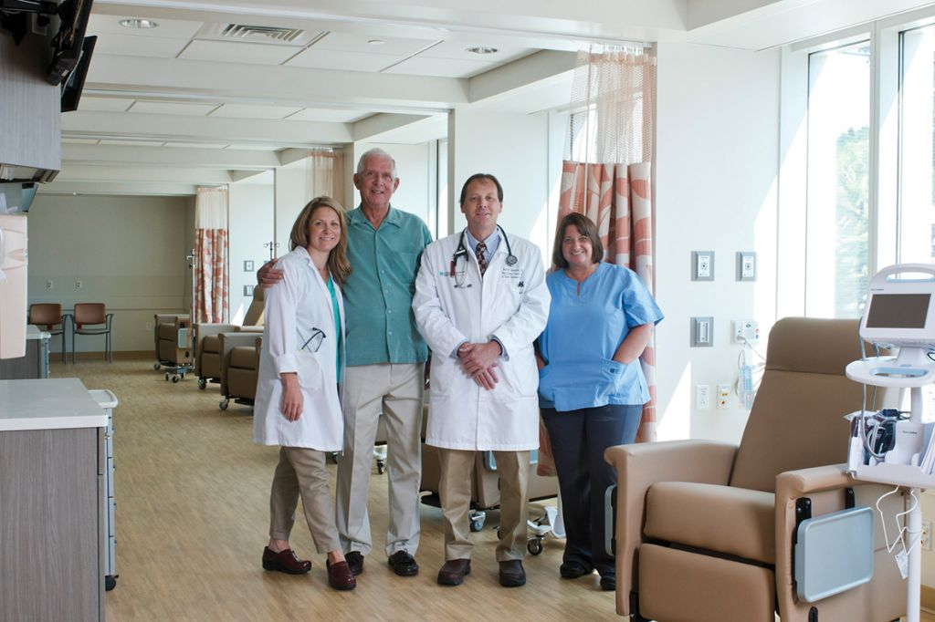 Patient with care team members Becky Puchalski, RN, Medical Oncologist Barrett Newsome, DO, and others at the Mass General Cancer Center at Cooley Dickinson Hospital.