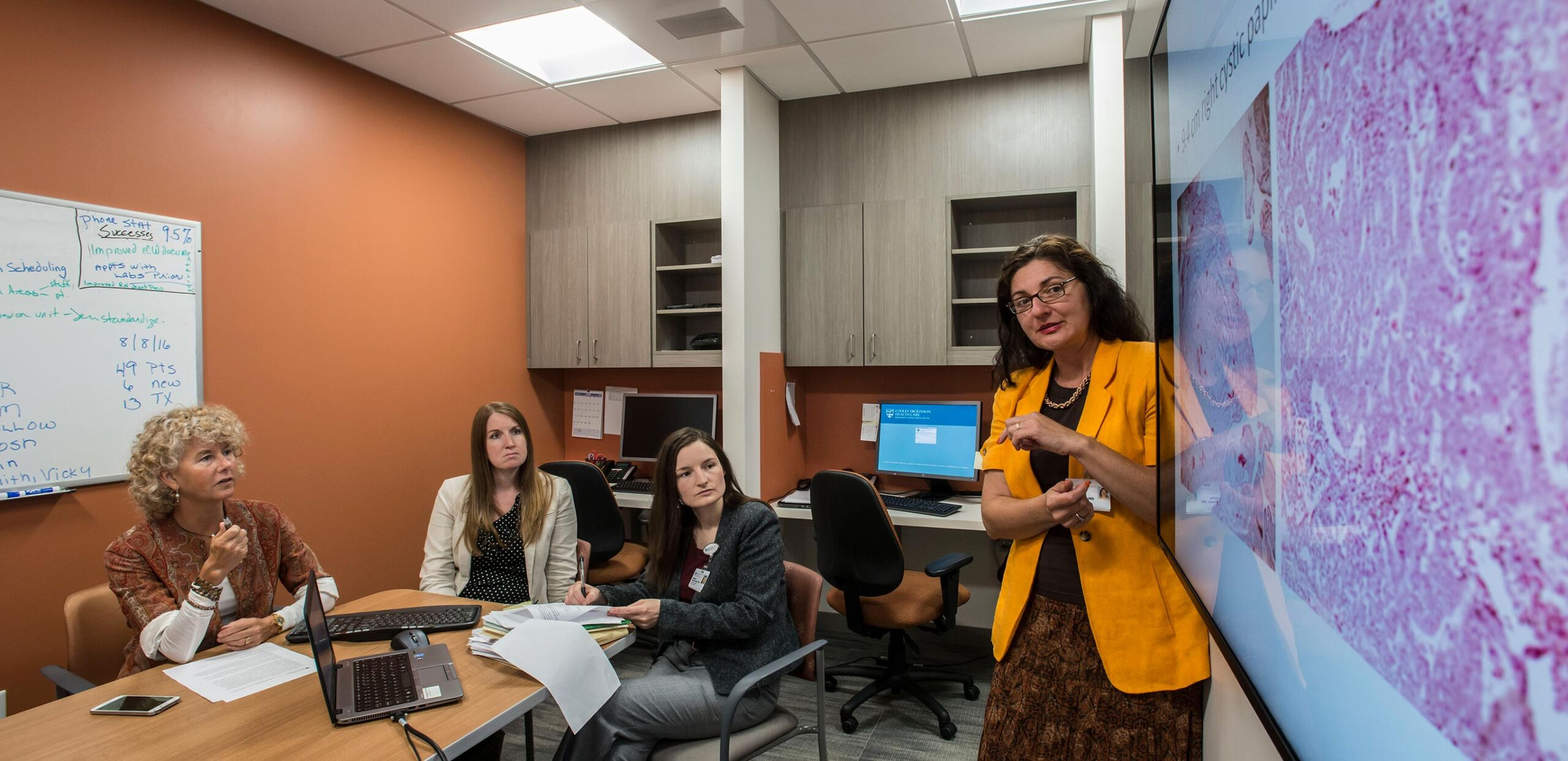 Marinescu, MD, reviews diagnostic images with Dhara MacDermed, MD, Michele Helms, MD, and Lindsay Rockwell, MD, at the Mass General Cancer Center at Cooley Dickinson Hospital, 30 Locust Street, Northampton, MA 01060.
