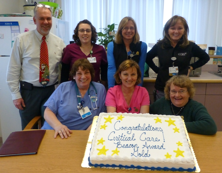 Members of the Cooley Dickinson Critical Care Team pose with a cake to celebrate the CCU's accomplishment of earning a gold-level Beacon Award for Excellence in Patient Care.