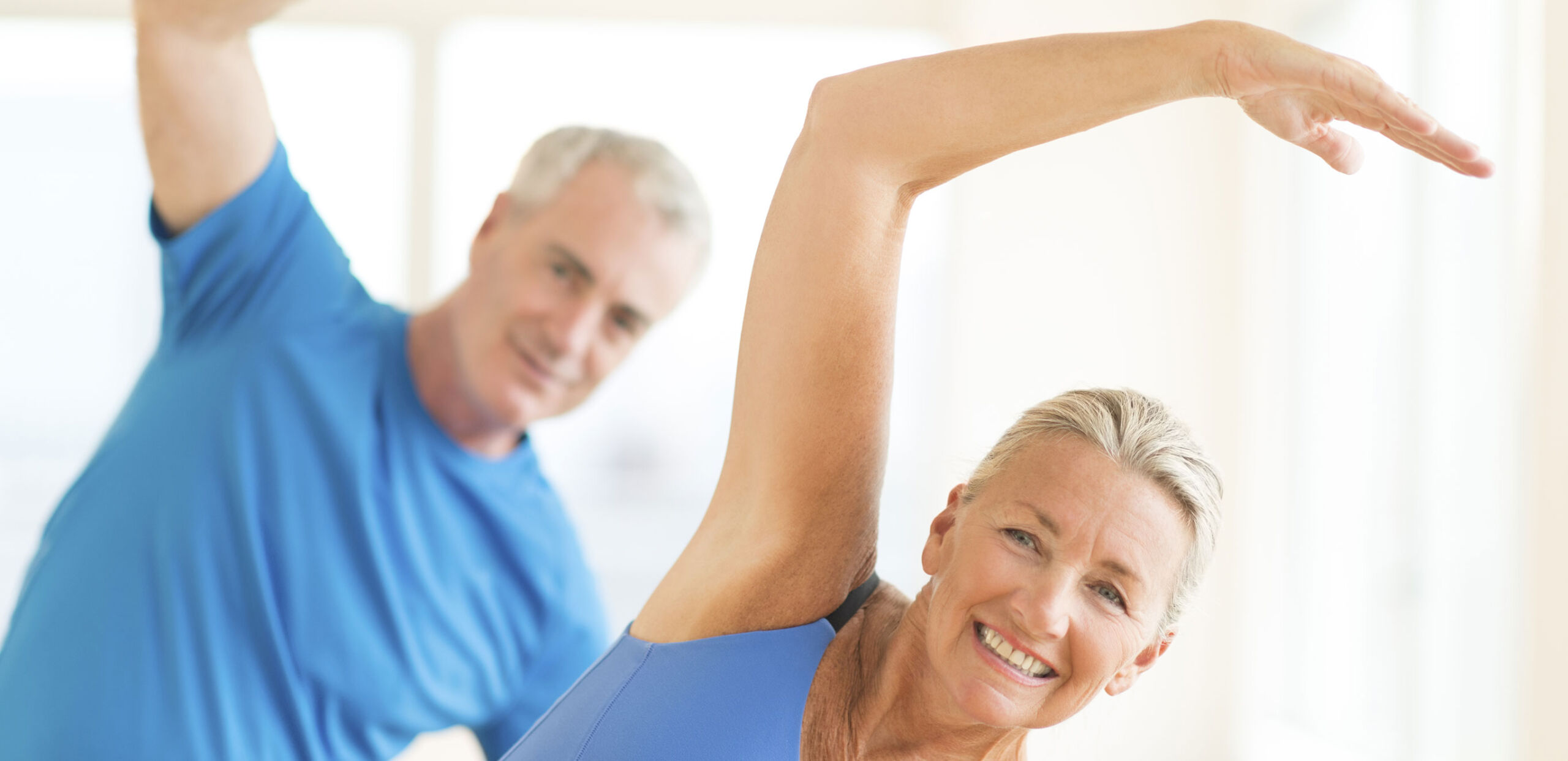 Middle-aged couple doing stretching exercises.