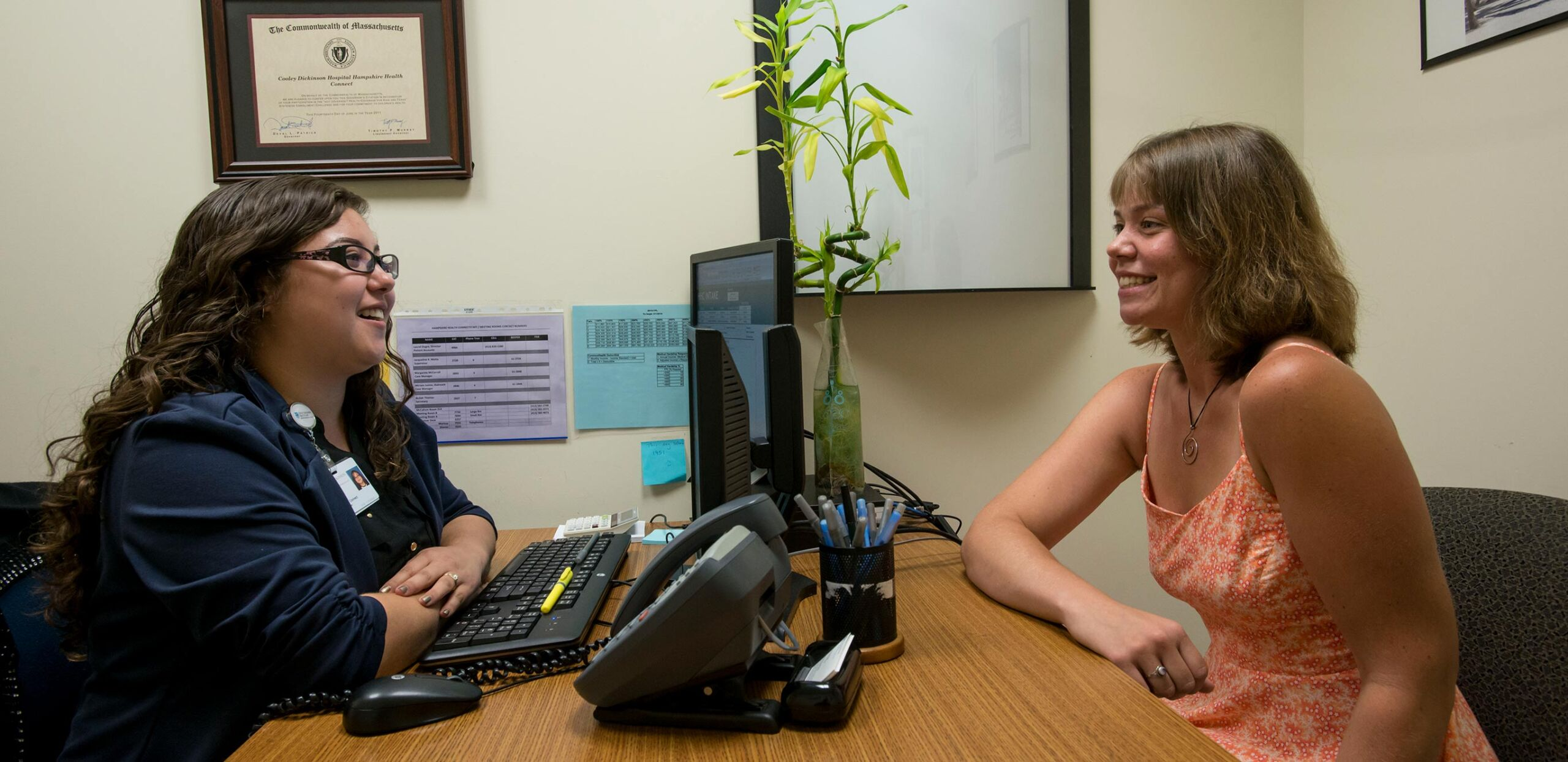 Female financial counselor talks with client in the Hampshire Health Connect office, Cooley Dickinson Hospital, Northampton, MA 01060