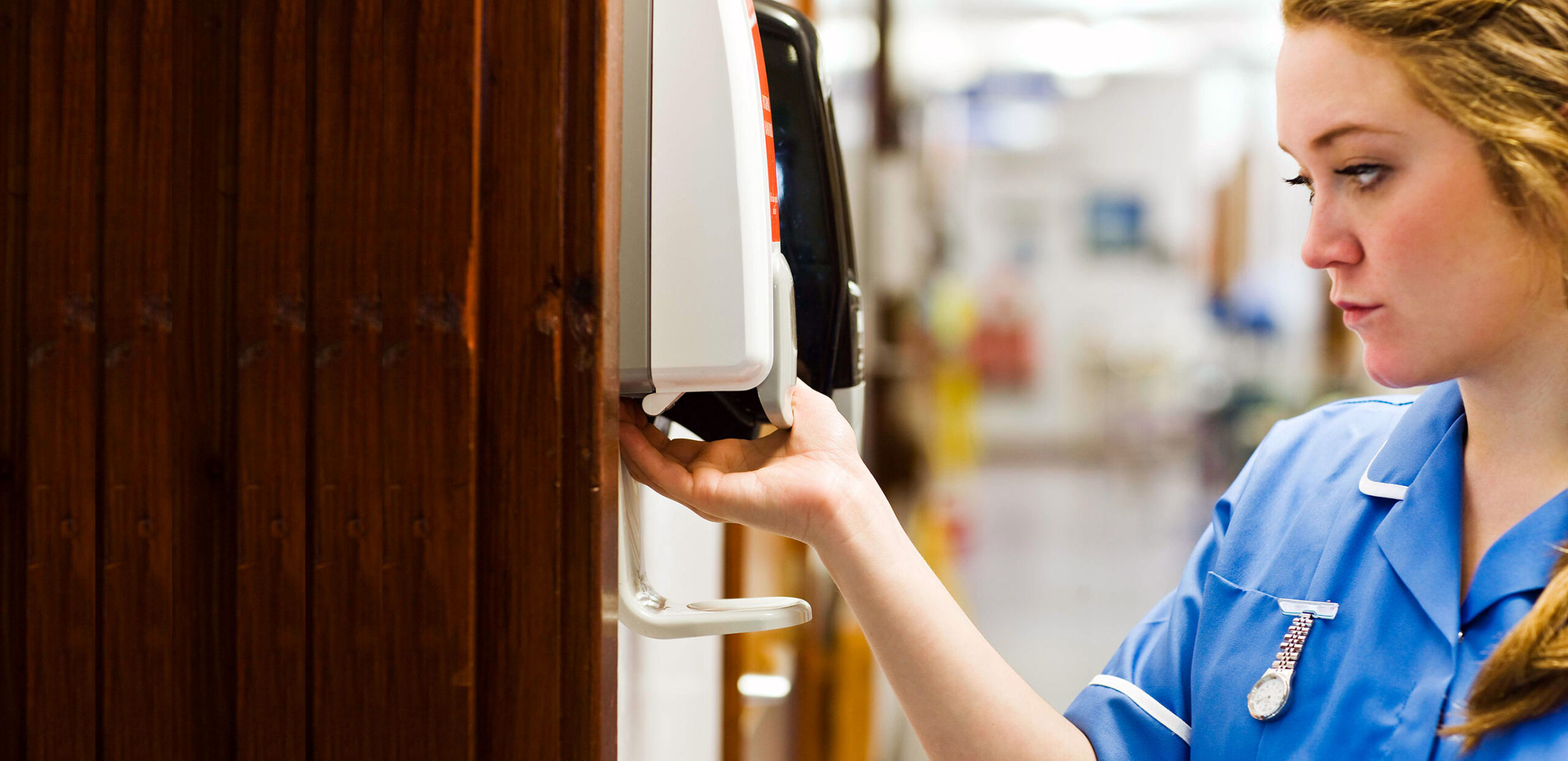 Nurse dispenses hand sanitizer from a wall-mounted dispenser, Cooley Dickinson Hospital, 30 Locust Street, Northampton, MA 01060.