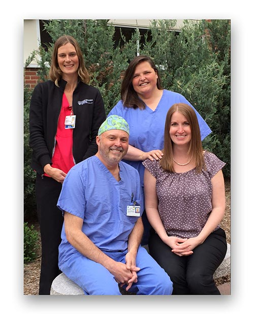 "From left, Kim Gibowicz, RN, Holly Michaelson, MD, and John Noviello, CRNA, with Michelle Helms, MD. In March, Michelle had emergency surgery to fix a perforation in her small bowel. Her CDMG General Surgery partner, Holly Michaelson, performed the surgery and was assisted by anesthetist John Noviello. Kim Gibowicz was one of the nurses who took care of Michelle while she was a patient on North 3. ""It's one thing to take care of patients; it's another thing to be a patient yourself,"" said Michelle."