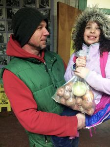 Maple Elementary School student June Halfacre and dad Jason receive their share of the School Sprouts Farm-to-School program's harvest-small-WEB